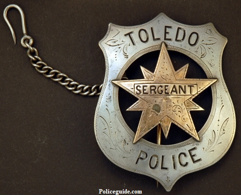 Toledo Police Sergeant sheild, made of sterling silver with applied gold front star and Sergeant designation.  Circa 1880.