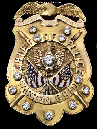 "Stunning 10k gold eagle topped shield, surmounted with a Phoenix rising above two American flags.  Twelve brilliant diamonds adorn the shield which is completed with crossed police batons. Marked ""Barney J. Gillen, Chief of Police, Warren, Ohio""."