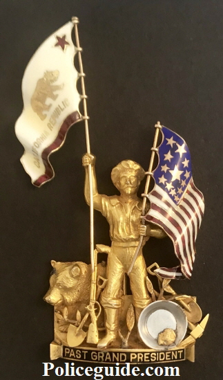 "Presented to San Francisco Police Judge Matt Brady, this 1929 California NATIVE SONS OF THE GOLDEN WEST styled 14k solid gold figural badge: ""GRAND PAST PRESIDENT."" These are extremely uncommon and were given out to special individuals within that group and rarely to others. The workmanship on this piece is superb with both the California Republic BEAR flag and the U.S. flag adorned with beautiful and detailed enameled work.  The theme of this piece is purely California depicting an imposing Figural GOLD MINER with his mining tools, next to an iconic California Grizzly Bear seated. Up against the miner is a gold pan with a natural native gold nugget.   The miner is gripping both flags in his two hands."