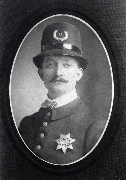Photo of a young John N. Black wearing San Jose Police badge No. 8 pie plate.